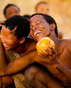Kalahari bushmen smiling holding melon