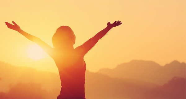 Girl with arms raised out at sunrise