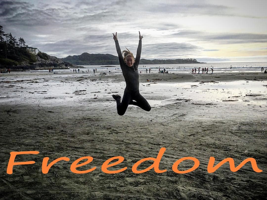 Girl jumping on beach with FREEDOM