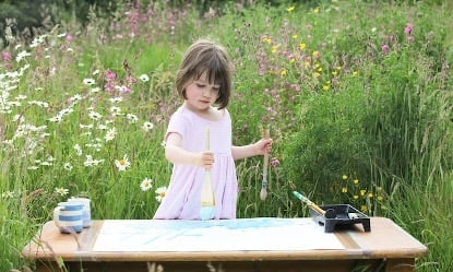 Little girl painting contentedly in a field with flowers